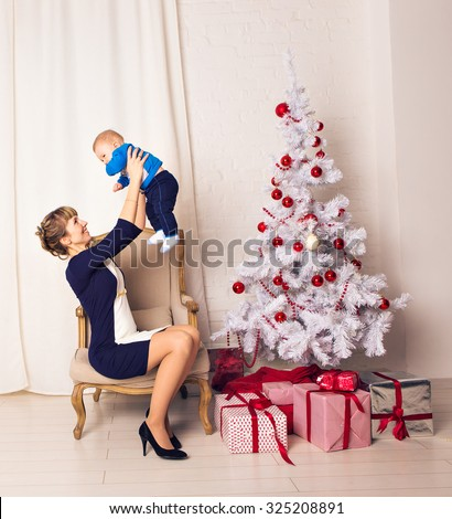 A happy mother holding her little son in her arms sitting on the armchair against the Christmas Tree - stock photo