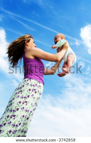 A happy mother raises her baby up in the air.