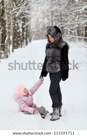 A happy mother walking with her daughter in winter Park