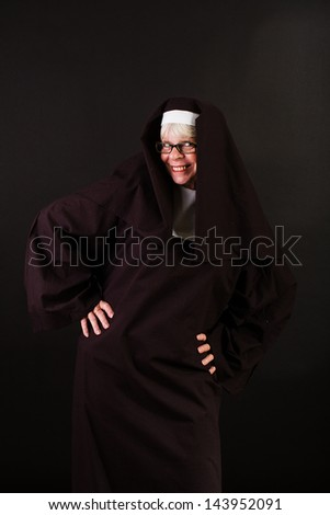 A happy nun with hands on her hips - stock photo