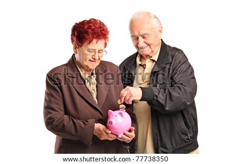 A happy old couple putting a coin into a piggy bank isolated on white background - stock photo