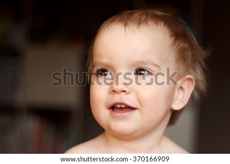 A happy one year blond boy smiling and looking aside, close-up emotional portrait, indoor