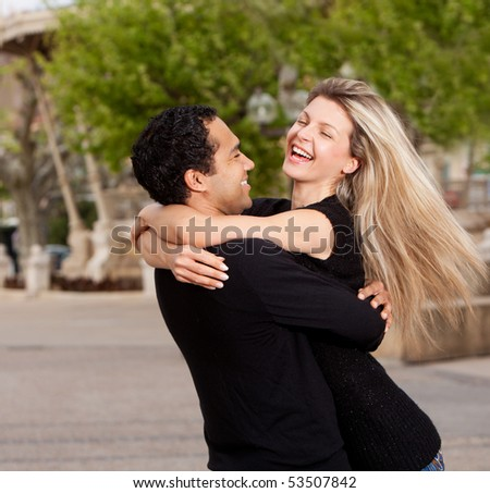A happy playful couple in an urban setting - stock photo