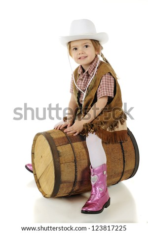 A happy preschool cowgirl straddling a rustic wood barrel as if it were a horse.  On a white background. - stock photo