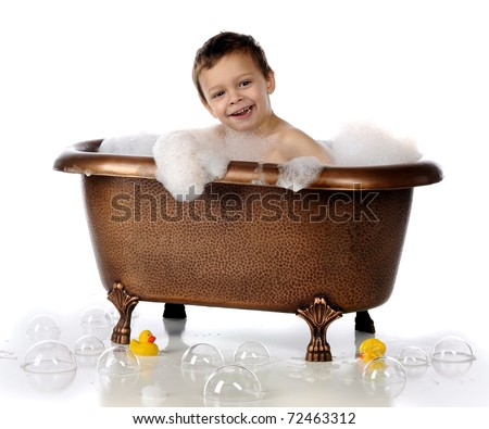 A happy preschooler playing in a copper, claw-foot bathtub filled with bubbles.  Isolated on white. - stock photo