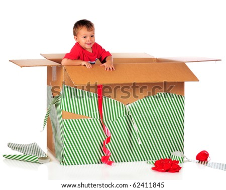 A happy preschooler playing in a giant-sized boy with the left-over wrappings from Christmas.  Isolated on white. - stock photo