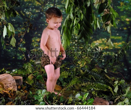 A happy preschooler playing Tarzan in a jungle-like setting. - stock photo