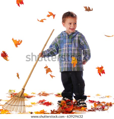 A happy preschooler raking while autumn leaves fall.  Isolated on white.  Some motion blur on falling leaves. - stock photo