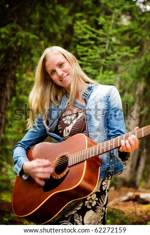 A happy pretty woman with a guitar - stock photo