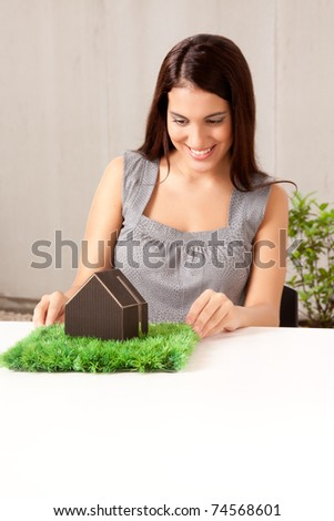 A happy professional woman looking at a model house with grass - stock photo