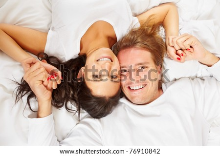 A happy romantic couple pose on white covered bed, showing their love for each other