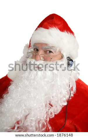 A happy santa claus listening to music through headphones. Isolated on white.