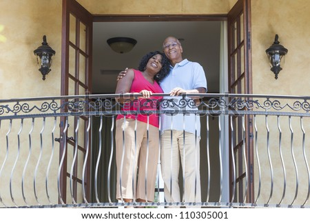 A happy senior African American man and woman couple in their sixties outside together smiling on a hotel or villa balcony - stock photo
