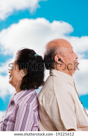 A happy senior asian couple listening to music outdoor - stock photo