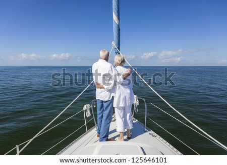 A happy senior couple embracing at the front or bow of a sail boat on a calm blue sea looking to an clear horizon - stock photo