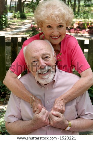 A happy senior couple embracing outdoors.  They are still in love after many years together. - stock photo