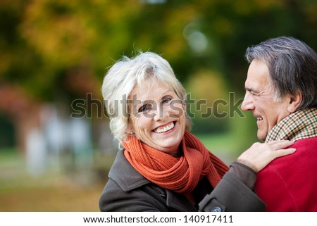 A happy senior couple enjoying a moment of love in the forest - stock photo