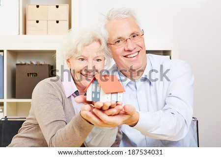 A happy senior couple holding a small house in their hands - stock photo