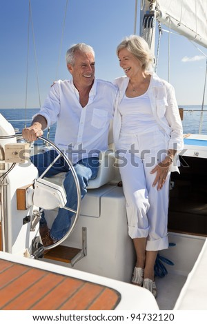 A happy senior couple sitting at the wheel of a sail boat on a calm blue sea - stock photo