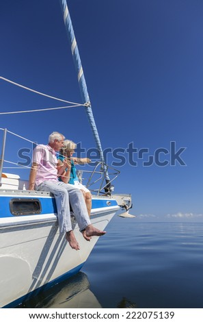 A happy senior couple sitting on the side at the front or bow of a sail boat sailing a yacht on a calm blue sea looking to an clear horizon