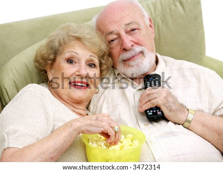 A happy senior couple with the remote control and the popcorn, ready to watch television. - stock photo