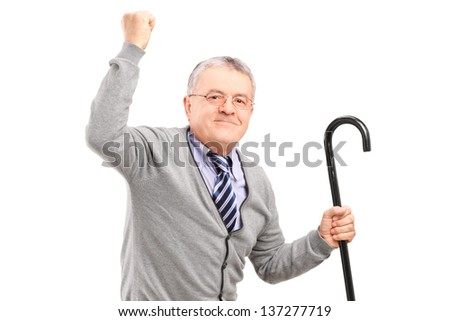 A happy senior man holding a cane and gesturing happiness isolated on white background - stock photo
