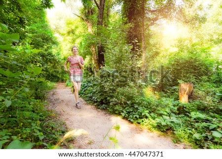 A happy senior woman is running toward the light in the forest during a warm summer day