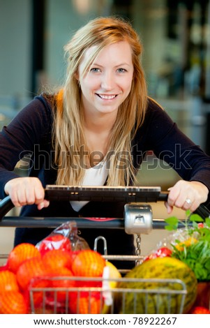 A happy shopping woman with grocery cart full of fruits and vegetables