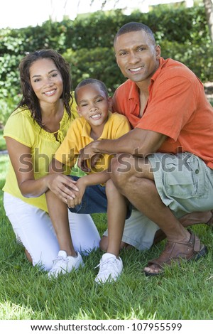 A happy, smiling African American family, mother father & son, man woman & child, outside in summer sunshine.