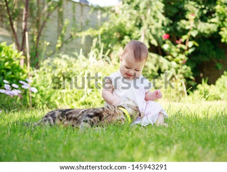A happy smiling baby in a dress playing with a cat in the garden - stock photo
