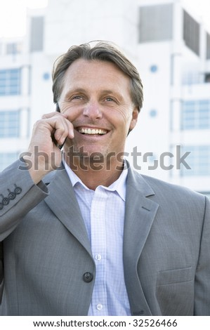 A happy smiling businessman chatting on cellphone. - stock photo