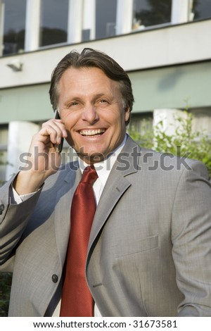 A happy smiling businessman chatting on his cellphone. - stock photo