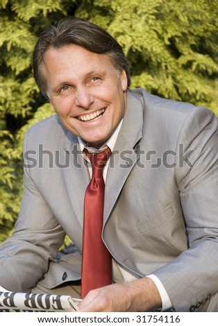 A happy smiling businessman reading a newspaper. - stock photo