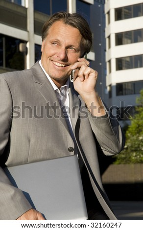A happy smiling businessman using cellphone and carrying laptop computer. - stock photo