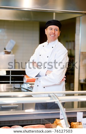 A happy smiling butcher helping a customer at a fresh meat counter - stock photo