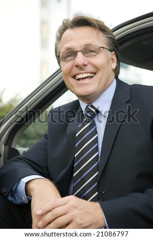 a happy smiling forties businessman wearing spectacles is sitting in his car - stock photo