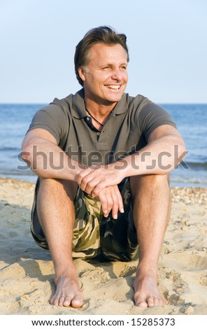 A happy smiling forties man is enjoying his beach vacation. - stock photo