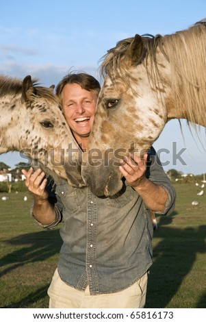 A happy smiling forties man petting two beautiful appaloosa horses.