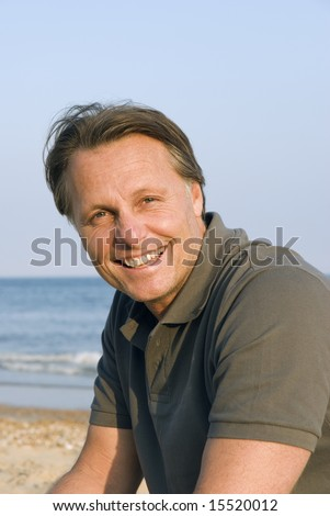 A happy smiling forties man relaxing on the beach.