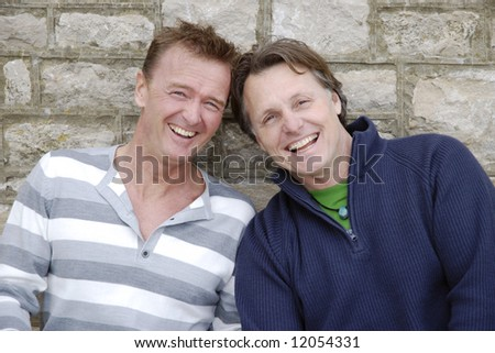 A happy smiling gay couple - stock photo