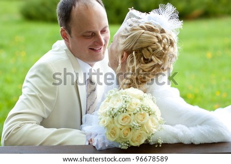 A happy smiling groom looking at a beautiful bride; wedding day - stock photo