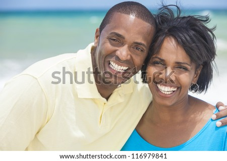 A happy smiling laughing African American man and woman couple at the beach in the summer - stock photo