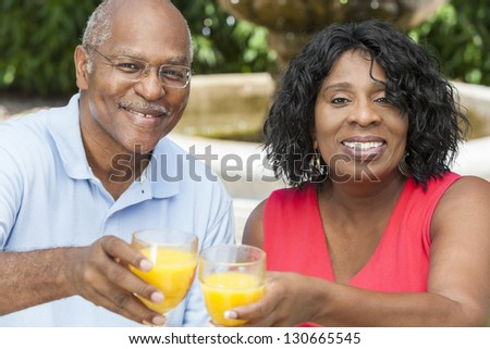 A happy, smiling man and woman senior African American couple outside drinking orange juice - stock photo