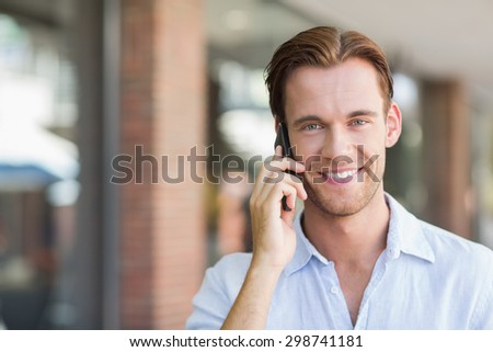 A happy smiling man calling at the mall
