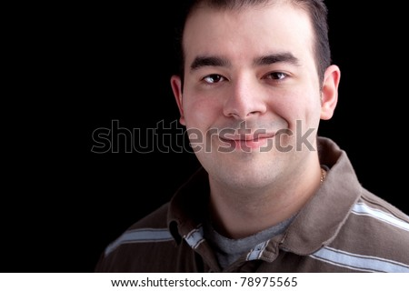A happy smiling man in his late twenties isolated over a dark black background.  Low key lighting technique. - stock photo
