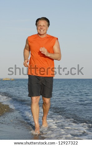 A happy smiling man jogging on beach.