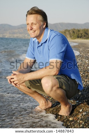A happy smiling man relaxing on a beautiful beach in Cyprus. - stock photo