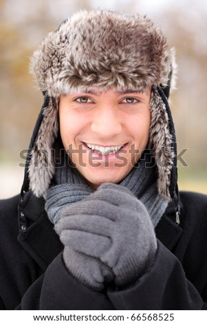 A happy smiling man wearing a fur trendy hat posing outdoor - stock photo