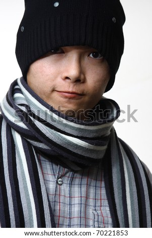 A happy smiling man wearing a hat and scarf posing against white background - stock photo