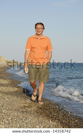 A happy smiling man wearing spectacles walking along a beautiful beach.